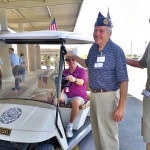 Dedicating the new golf cart at the Southeast Clinic of the VA in Gilbert are (right to left) Art Sharff and Eliott Reiss with small bottle of champagne along with other veterans.