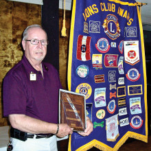 "District Governor Elect Lion Larry Palmer of the Sun Lakes Lions Club proudly stands by one of the club's banners with his ""Lion of the Year"" award plaque. Presented by Club President Forrest Cheuvront earlier, Lion Larry stands out in how he follows the Lions Motto of ""We Serve."" He will be sworn in as District Governor of Arizona's 21-B in July at the International Lions Clubs Convention held in Toronto Canada."