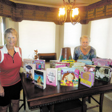 VFW Auxiliary President Betty Peer and Veterans and Family Support Chair Sandra Whittenberg with educational materials purchased for children of the adopted Guard unit member who was killed in an auto accident.