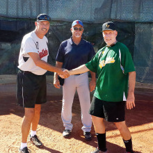 Managers Steve Hilby of Terry & Susan Young's West USA Realty team and Ken Brenden of Brenden Financial Services meet before a recent game as umpire Gary Hillabolt looks on.