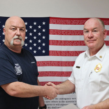 Captain Brad Rock is congratulated by Chief of Department Paul Wilson