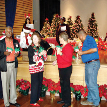 San Tan Crown Rotary members Bob Craft, Barbara Brooks, Joann Knutson and James Kame pass out Christmas cards and Rudolph candy canes at the Sunshine Residential Homes annual Christmas party.