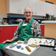 """Jim Remer is shown here with some examples of Lapidary. In the foreground are """"slabs."""" These are flat portions that were cut with stone saws from larger stones (sometimes as large as 24 inches thick). Slabs are inspected for quality, further cut with smaller stone saws, then shaped and polished on grinding wheels to become beautiful gems. These are then set in metal for wearable jewelry."""