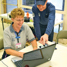 Sun Lakes Fire Department Battalion Chief Rob Helie points out an important part of the flash drive medical forms to CAP member Nancy Roberts.