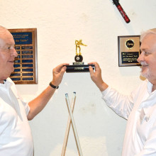 """David """"The Godfather"""" Mork, IronOaks Breakers Pool League and Conrad Leines, Mission Royale Billiards, holding the shelf which has on it the 8-Ball """"Winner's Traveling Trophy"""" in the IronOaks Pool Room."""