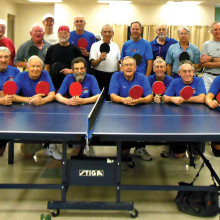The victorious Saddlebrooke team displays the red paddles. The Sun Lakes Table Tennis Club members display the black paddles.