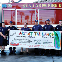 Artist Susan Plouzek painted the banner and additional signs to advertise the show. Pictured with Susan are the firemen from Sun Lakes Station No. 231.
