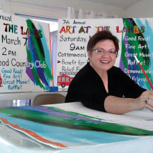 Susan Plouzek paints signs for Art at the Lakes in her studio.