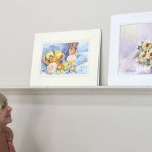 Joyce Ennis admires paintings awaiting critiques