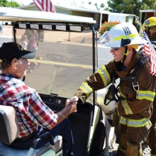 Battalion Chief Rob Helie thanks a Sun Lakes World War II veteran for his service as the gentleman cheered the SLFD group on.
