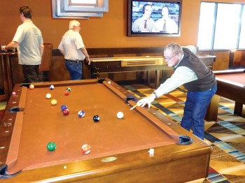 League member Willie Foster playing pool in the Billiards Room at Robson Ranch, Casa Grande, with Keith McDonald and Fritz Derheim in the background.