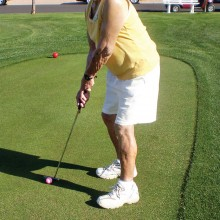 Susan Powell is taking a practice shot as she prepares for a morning round with her Lady Putters group.