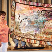 "Denny Sullivan shows the Agave Guild her ""Great Blue Heron"" quilt. This was made in memory of her brother who helped protect a Heron rookery in Vermont several years ago."