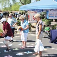 Yippee, I'm in the lead; seniors try out the horse race at the annual Community Fair.