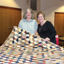 October speaker Shirley Weagant shows one of her beautiful antique quilts to Agave member Susie Seckel.