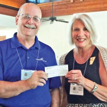 Eric Ehst receives an $800 check from Ocotillo Women's League Community Chairman Cheri Morgan.
