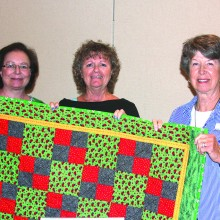 Gwen Oberg, Jean Larson and Sherri Tanner hold one of the kids quilts headed to hospitals.