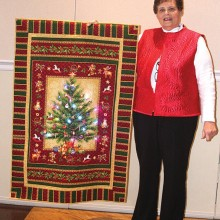 Judith Kraker, Agave member and professional quilter, shares her delightful light-up Christmas quilt with attendees at the holiday party.
