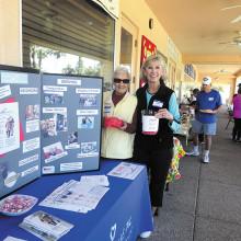 Raffle coordinator Betty Sanders and IronOaks Tennis Club President Judy Gahide raising money for Neighbors Who Care.