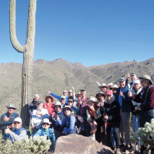 Hikers give a thumbs up salute while standing in front of Tom's Thumb rock formation.