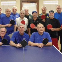 Winning Sun Lakes table tennis players with their paddles turned to the red side and losing SaddleBrooke table tennis players with their paddles turned to the black side.