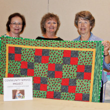 The Agave community service team shows off one of the many children's quilts donated by members.