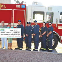 Sun Lakes Emergency Relief Fund check is presented to firefighters. Pictured left to right are Pat Merkle, Diane Hitt, Gary Neffenger, Susan Plouzek, Brandon Johnson, Martin Lain, Andrew Craker, Ari Barr and Nate Van Briesen.