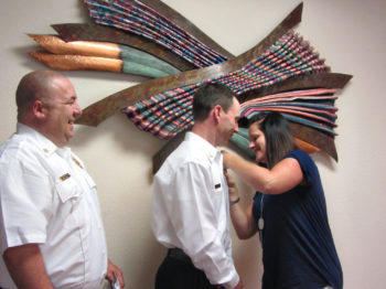 Sun Lakes Fire District Chief Troy Maloney (left) beams as Shawn Helie, wife of newly promoted Deputy Chief Rob Helie, pins his new Deputy Chief's badge on him. Deputy Chief Helie has risen through the SLFD ranks and takes over for retiring Deputy Chief Dan Guerra. (Photo by LouAnn Sedgwick; caption by Brian Curry).