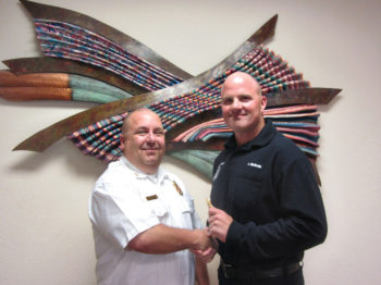 Sun Lakes Fire District Troy Maloney (left) congratulates new Battalion Chief John McBride. McBride, who has been an acting battalion chief for the last several months, was promoted due to Battalion Chief Rob Helie's promotion to Deputy Chief. Not pictured is newly promoted Battalion Chief Robert Olmsted. These promotions fill out the SLFD command structure. (Photo by LouAnn Sedgwick; caption by Brian Curry).
