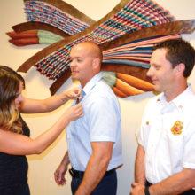 Deputy Chief Rob Helie smiles as Allie, wife of new engineer Adam Flynn pins his badge