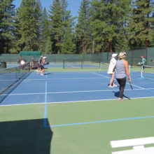 Pickleball players in Incline Village, Nevada playing on double striped tennis court.