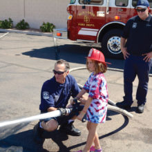 """Firefighter Craig Daniels lets this young girl get a chance to put out the """"fire."""" Firefighter Brandon Johnson watches."""