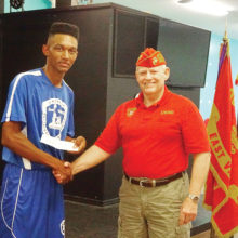 Young Marine SSgt. Tyson Henry receives a donation from East Valley Marines Sr. Vice Commandant Dave Lott.
