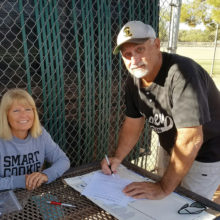 """Cyndy Hilby """"mans"""" our sign-up table as Gary Hillabolt fills out his application for the 2016-17 softball programs."""