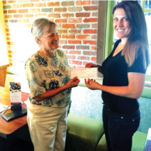 PCE grant recipient Elizabeth Mollenhour is presented a check by Becky Paschal-Snyder of Chapter DD.