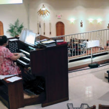 Sun Lakes resident Bill Bade conducts the Risen Savior Chancel Choir, Hand Bell Choir, and instrumentalists in the award winning Easter Sunday performance of James Chepponis' Christ Is Risen. Carla Robertson accompanies on the organ (photo by John Freund).