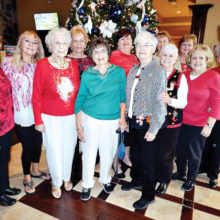 Ladies Billiards Club members gather in front of the Christmas tree before their annual Christmas luncheon at Stone & Barrel.