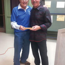 Karl Kern (right) receives a pen from Gary Vacin, Sun Lakes Aero Club program director, following Kern's presentation to a SLAC gathering January 16; photo by J. R. Scheidereiter