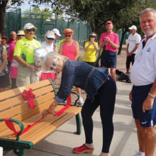 Sandy Neu cuts ribbon on dedicated bench as project coordinator, Bruce Stead, looks on