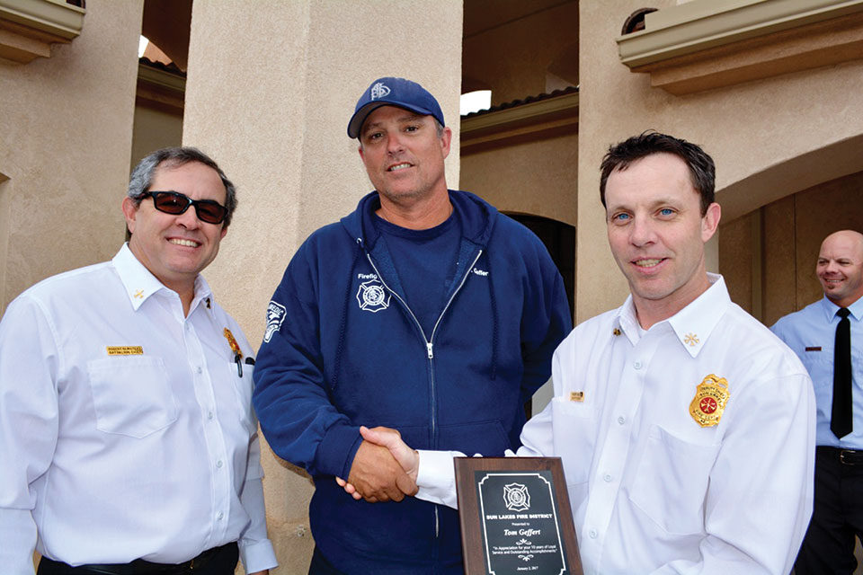 Sun Lakes Fire District Battalion Chief Robert Olmstead (left) and Deputy Chief Robert Helie (right) congratulate firefighter/paramedic Tom Geffert on his 10th anniversary with SLFD. Geffert has served as an acting Captain and Engineer and is as a member of the SLFD Wildland fire team. Photo by Brian Curry.