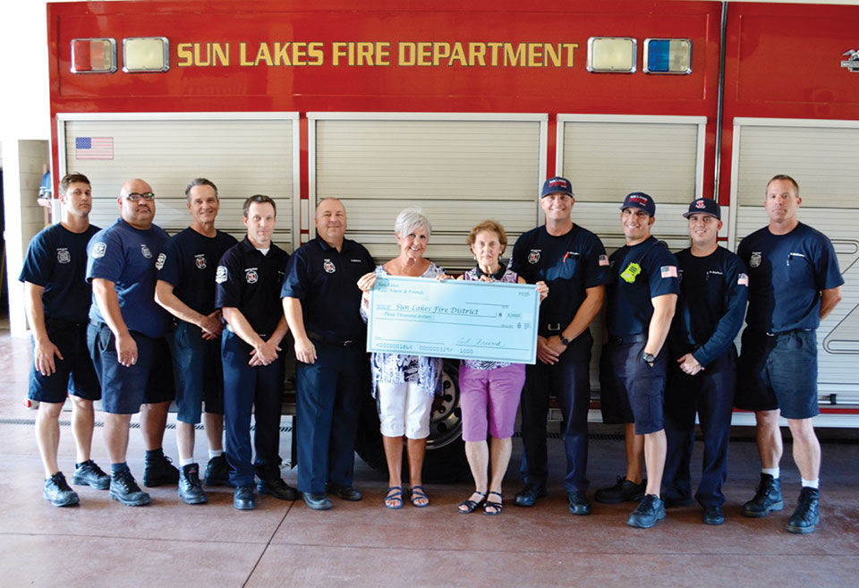 Sun Lakes Lady Niners Secretary/Party Chair Sheila Barton and 1st Vice President Celeste Dorsey present a check for $3,000 to the Sun Lakes fire district, including Chief Troy Maloney and Deputy Chief Rob Helie and the on-duty firefighters and medics from the SLFD's stations.