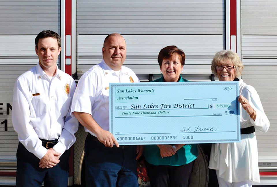 """Pictured (left to right): Sun Lakes Fire District Deputy Chief Rob Helie and Chief Troy Maloney are presented a """"check"""" for $39,000 for the purchase of state-of-the-art emergency band radios by Sun Lakes Women's Association President Judy Caniglia and Vice President Marjorie Shipe."""