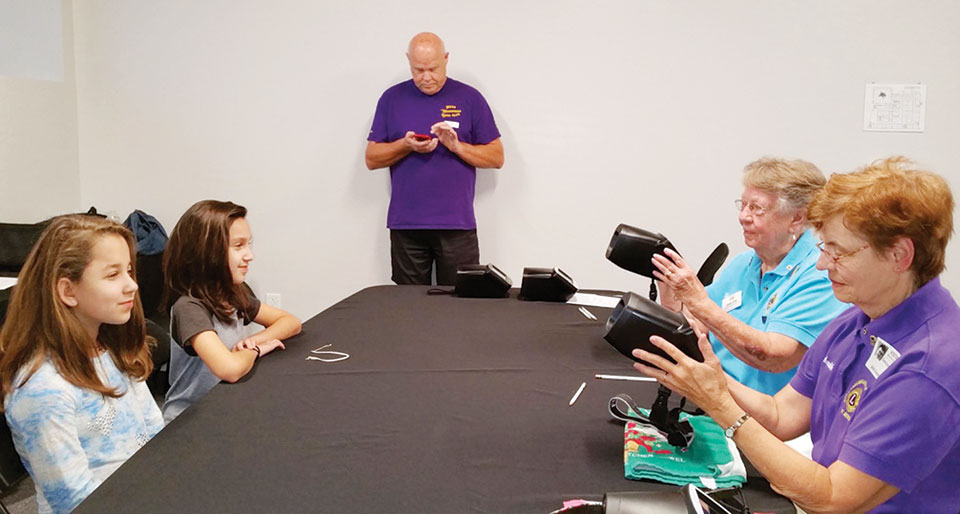 """Sun Lakes Breakfast Club Lions Donna Quinn (in light blue shirt) and Sue Schauble (in purple shirt) administer a vision screening test to two students of the Chandler BASIS Charter School using the """"SPOT"""" machine which screens for various eye problems."""