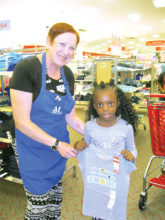 April Joy of Sun Lakes helps Lauren Perkins, a second grader at Webster Elementary in Mesa, pick out a new outfit.