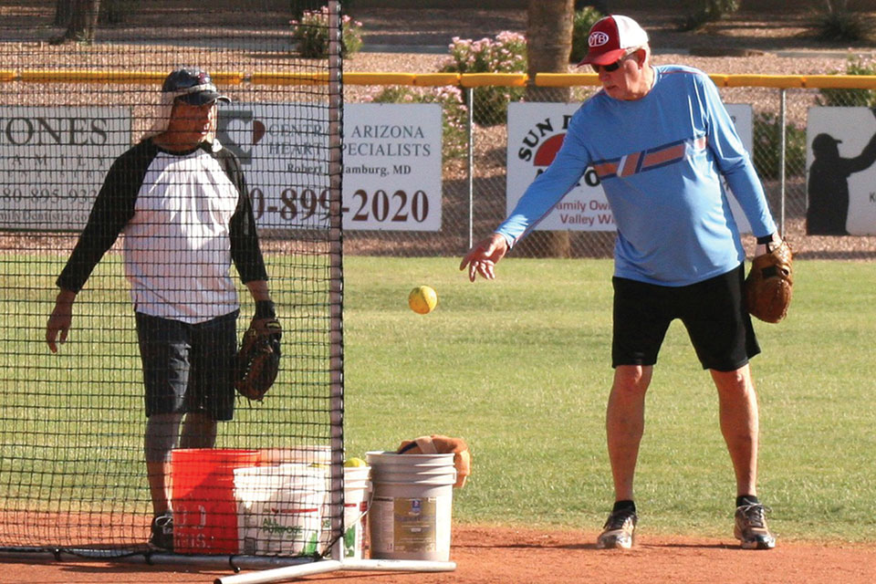 Reyes Gonzales and Randy Rothenbuehler gather softballs at summer batting practice. Now it's time for the real thing! (Photo by Core Photography)