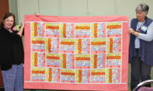 "Jeannie Sanders (left) and Sue Bart (right) display a ""Rail Fence"" quilt."