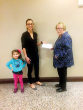 """Geri Hall from P.E.O. Chapter DD, Sun Lakes, presents PCE grant recipient Melissa Leffler (with daughter """"Izzy"""") with the P.E.O International Grant Award for Continuing Education."""