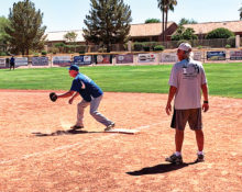 "First baseman Dean Messier awaits a throw while first base coach ""Hoot"" Gibson looks on. (Photo by Core Photography)"