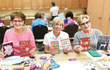 Pat Krafcik, Virginia Diers, and Kathy Skrei show some of the holiday cards available from The Crystal Card Project.