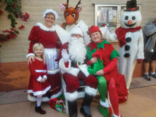 Pictured from left to right are Caitlyn Ortbahn - Mr. and Mrs. Claus' granddaughter; Julie Ortbahn (real grandmother to Caitlyn) – Mrs. Claus; Santa – Bill Carpenter; MJ Clement – Rudolph the Red Nosed Reindeer; Merrie Crawford – Elf; and Wanda Johnson – Frosty the Snowman. Running around in the crowd somewhere was Elf Joyce Recupido.